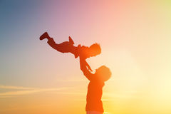 Father and little son silhouettes play at sunset Stock Photography