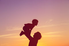 Father and little son silhouettes play at sunset sky Royalty Free Stock Photography