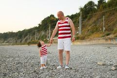 Father and little son in similar clothes look at together. Father and 2 years son in similar clothes look at together Royalty Free Stock Image