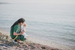 Father and little son sitting near the ocean. At the beach Stock Photography