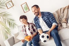 Father and little son at home sitting on sofa boy holding potato chip dad with ball watching football smiling joyful royalty free stock photo