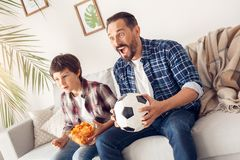 Father and little son at home sitting on sofa boy holding potato chip and dad with ball watching soccer shouting excited stock photography
