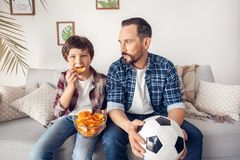 Father and little son at home sitting on sofa dad with ball looking at boy holding potato chip watching football smiling stock photography