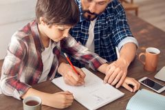 Father and son at home sitting at table dad showing boy how to do math exercise close-up stock photography