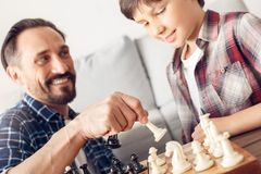 Father and little son at home sitting at table playing chess dad capturing boy`s piece joyful close-up. Father and little son together at home sitting at table stock images