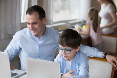 Father and little son using laptop sitting at home. Happy family with small children spend free time together at home. Little son copying father sitting at the stock image