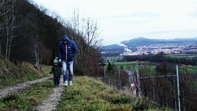 Father and little son are walking along a mountain path. Little boy in warm jacket and hat holding father's hand stock video