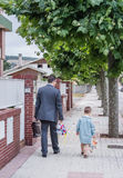 Father and little son walking on the street to the school stock photography