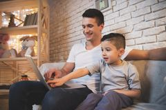 Father and little son are watching movie on laptop at night at home. Father and little son are watching movie on laptop on couch at night at home Stock Photos