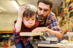 Father and little son with wood plank at workshop Royalty Free Stock Photography
