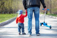 Father and little toddler son on a spring walk with a blue kick scooter. Kid is holding hand of father. Active family on a walk. Little toddler boy on a walk stock photography
