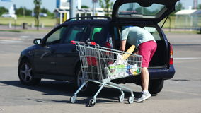 Father loading foods from shopping cart into car trunk at parking lot. The role of men in the family. Distribution of stock footage