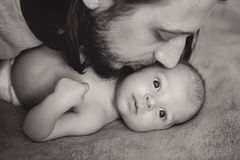 Father long hair kissing his son. Lying on the bed stock images
