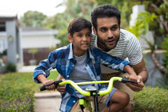 Father looking away while assisting son for cycling Royalty Free Stock Images