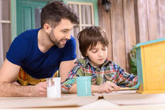 Father looking at concentrated little son painting wooden birdhouse on table Royalty Free Stock Photography