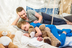 Father looking at cute little son sleeping with teddy bear in blanket fort Royalty Free Stock Photos