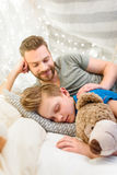 Father looking at cute little son sleeping with teddy bear Stock Image