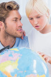 Father looking at globe with his son Royalty Free Stock Photos