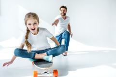 Father looking at happy daughter sitting on skateboard Royalty Free Stock Images
