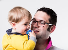 Father looking at his son sucking his pacifier Royalty Free Stock Photos