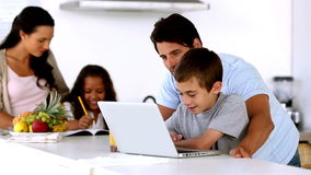 Father looking at laptop with son and mother enters to help daughter