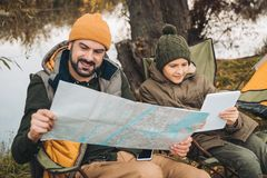 Father looking at map and son looking at tablet sitting. On camp-chairs stock photo