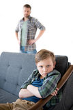 Father looking at serious little son sitting on sofa with crossed arms. Family problems concept Royalty Free Stock Image
