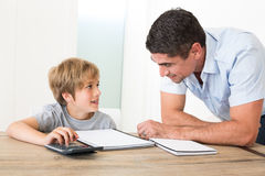 Father looking at son doing homework. At home Stock Images