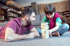Father looking at son playing jenga game. Low angle view of father looking at son playing jenga game Royalty Free Stock Photos