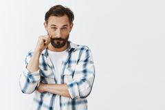Father looking suspiciously at son who came late, making strange accuses. Dubtful attractive mature male with beard. Touching moustache and staring with stock photography