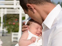Father love. Concept - father kissing his newborn baby daughter Stock Photos