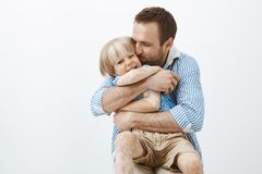 Father loves his little son like no one else. Cute good-looking caring dad hugging and kissing child in cheek, feeling. Happy spending time with kid, standing royalty free stock photo