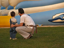 Father Loves His Son. Father with his son in the fun park in front of air slide Royalty Free Stock Photo