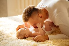 Father lying on bed and holds his baby. Young Father lying on bed and holds his baby Royalty Free Stock Photos