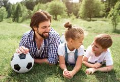 Father is lying on grass on meadow with children. He is holding ball with hand. Man is looking at his son with his. Daughter. Boy looks happy and funny royalty free stock photography