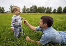 Father lying on his stomach tickles son 1.3 years with  sprig . Royalty Free Stock Photos
