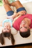 Father Lying Upside Down On Sofa With Daughter Royalty Free Stock Photos