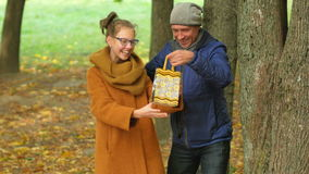 Father makes daughter a surprise gift for his birthday. Dad handed the teenager a present in a beautiful autumn forest.  stock footage