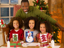 Father making Christmas cards with children. African American father making Christmas cards with children royalty free stock photos