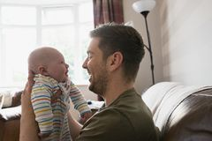 Father Making His Baby Laugh. Father holding his new born baby boy up to his face to make him laugh. They are sitting in the living room on the sofa stock photography