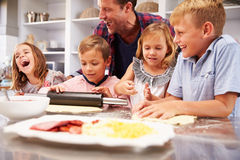 Father making pizza with his kids Stock Photography