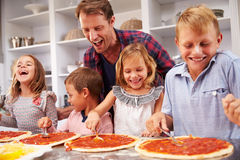 Father making pizza with his kids Stock Images