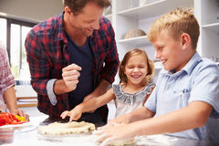 Father making pizza with kids Royalty Free Stock Photos