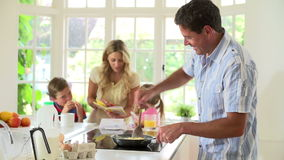 Father Making Scrambled Eggs For Family Breakfast In Kitchen
