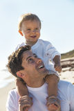Father Man With Baby By Child on Shoulders at Beach Stock Image