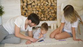 Father man mother helping their child draw picture in their living room stock footage