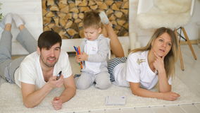Father man mother watch TV while their son draw picture in their living room stock footage