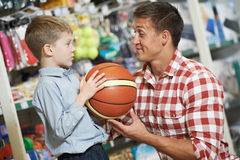 Father man with son boy shopping sport goods. Family shopping. Young father with son choosing sport equipment basket ball at supermarket Royalty Free Stock Photos