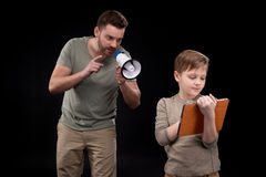Father with megaphone screaming at little son using digital tablet Royalty Free Stock Image
