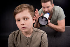 Father with megaphone screaming at scared little son Stock Photo